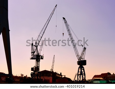 Hamburg Harbor in the sunrise or sunset. Freight shipping cranes.