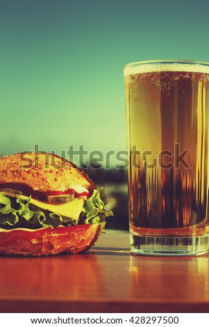 hamburger and a glass of beer against the backdrop of the modern city and blue sky. VINTAGE - stock photo