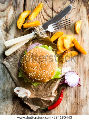 hamburger and fries on a wooden table. view from above
