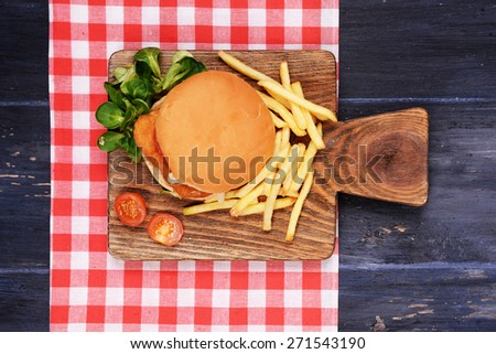 Hamburger, french fries and tomato on wooden table top view - stock photo