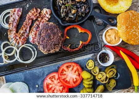 Hamburger, homemade hamburger, bacon and grilled vegetables - stock photo