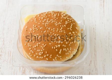 hamburger in plastic box on white wooden background - stock photo