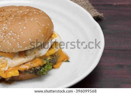 hamburger in plate on wood table.