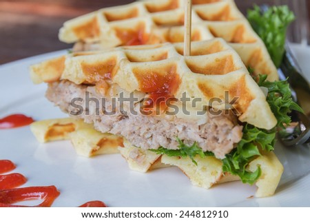 Hamburger made with waffles and pork on white plate.