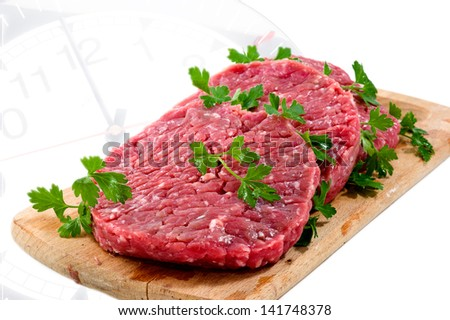 Hamburger of beef on wooden board with parsley on clock's background - stock photo