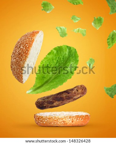 Hamburger of flying parts on yellow with orange background - stock photo