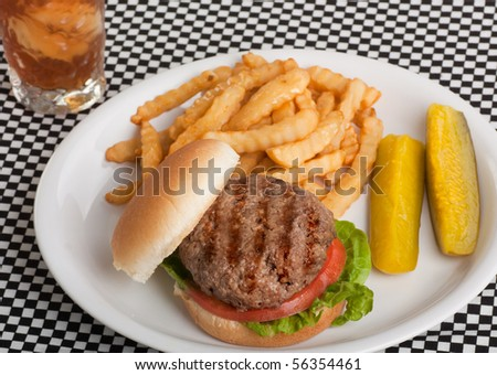 Hamburger on a bun with tomato and lettuce with french fries, pickles and a drink