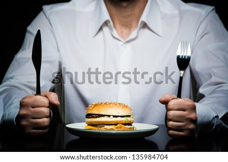 hamburger on a plate in front of a man holding fork and knife
