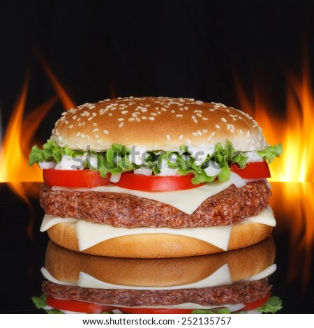 Hamburger on black background with reflection and real fire