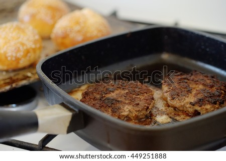 Hamburger patties fried in a grill pan. - stock photo