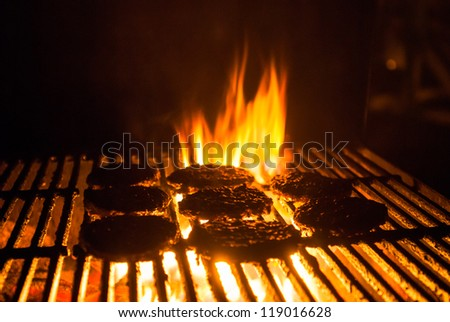 Hamburger patties grilling with charcoal barbeque flames - stock photo