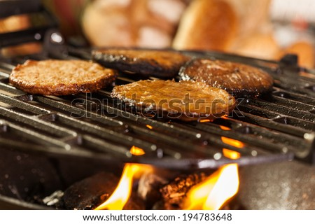 Hamburger patties on a grill with fire under. Selective focus - stock photo