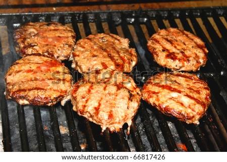 Hamburger patties on grill - stock photo