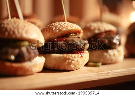 Hamburger sliders  on a rustic cutting wooden board. - stock photo