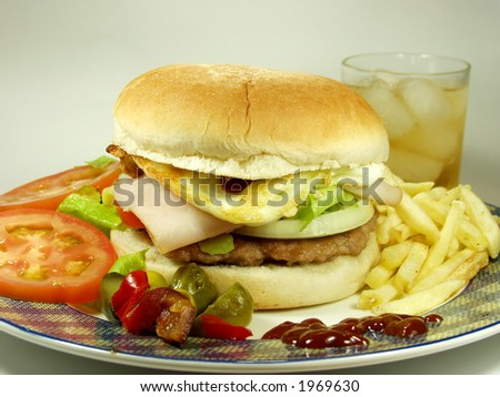 hamburger whit egg and french fried, salad and ice tea for drink