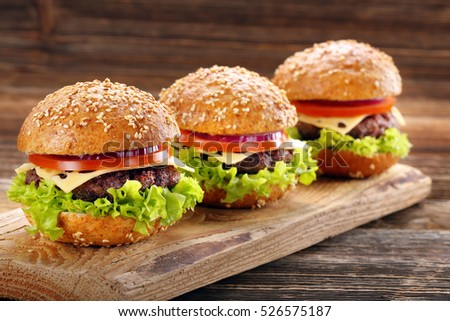 Hamburger with beef meat and fresh vegetables on wooden background