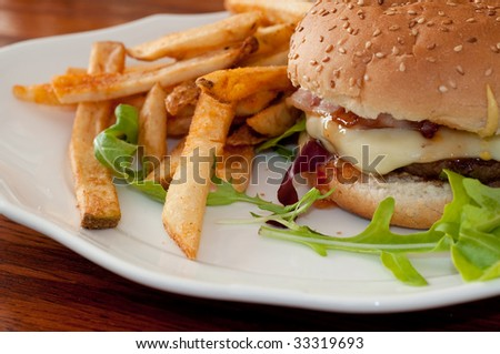 Hamburger with cheese and bacon with fries
