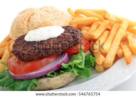 Hamburger with chunky blue cheese salad dressing, lettuce, tomato, and onion with plate of french fries.