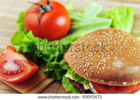 hamburger with cutlet and vegetables on bamboo napkin - stock photo