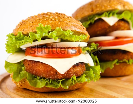 hamburger with fish cutlet and vegetables on wooden board on white background