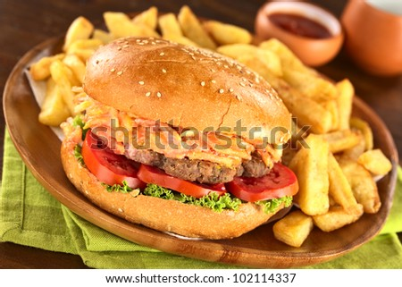 Hamburger with French fries on rustic wooden plate with ketchup (Selective Focus, Focus on the front of the hamburger)