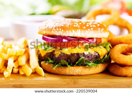 hamburger with fries and onion rings on wooden table - stock photo