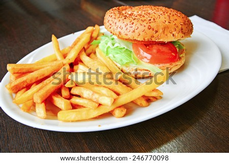 Hamburger with fries on the wooden table