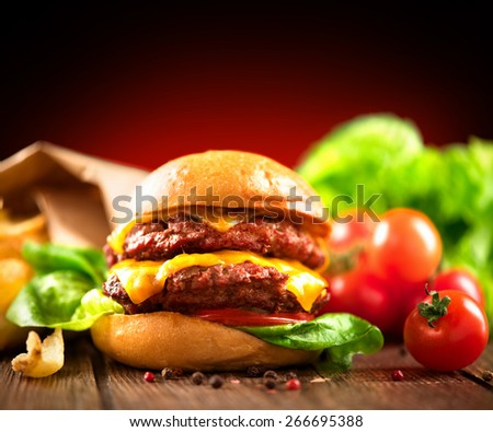 Hamburger with fries on wooden table. Cheeseburger on fresh buns with succulent beef patties and fresh salad ingredients served with French Fries on crumpled brown paper on a rustic wood table - stock photo