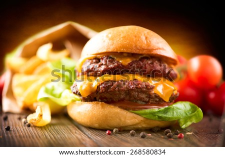Hamburger with fries on wooden table. Cheeseburger on fresh buns with succulent beef patties and fresh salad ingredients served with French Fries in crumpled brown paper on a wooden table - stock photo