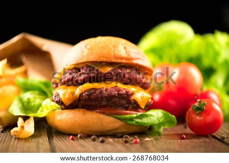 Hamburger with fries on wooden table. Cheeseburger on fresh buns with succulent beef patties and fresh salad ingredients served with French Fries on a wooden table - stock photo