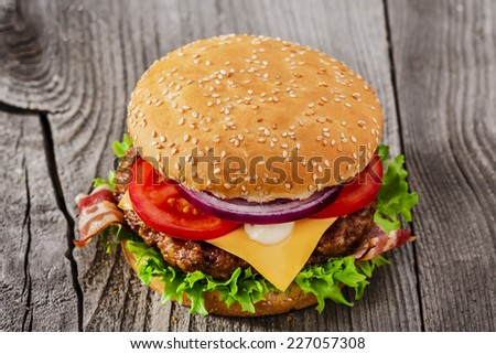 hamburger with grilled meat cheese bacon on a wooden surface