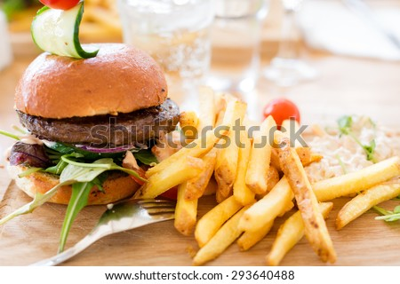 Hamburger with lettuce and french fries served on a wooden plate with a tight composition and short depth of field in a restaurant Environment. - stock photo