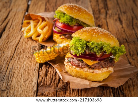 Hamburger with vegetable on wooden table