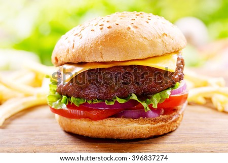 hamburger with vegetables and cheese on a wooden table