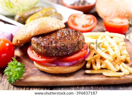 hamburger with vegetables and fries on a wooden table