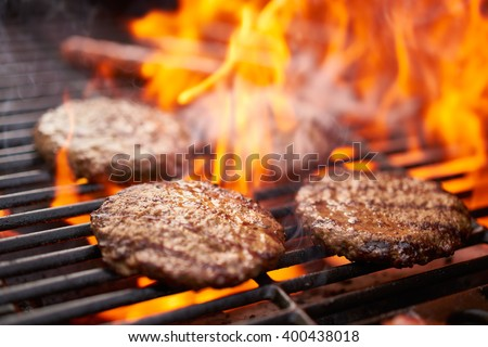 hamburgers and hot dogs cooking on grill with flames - stock photo