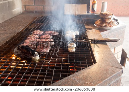 Hamburgers and vegetables being grilled