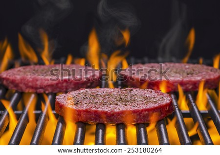 Hamburgers Cooking on a Hot Flaming grill - stock photo