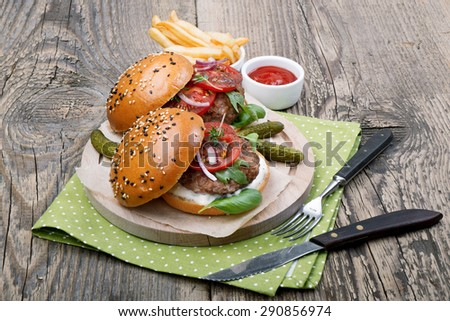 Hamburgers on sesame buns with succulent beef patties and fresh salad ingredients - stock photo