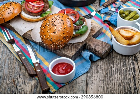 Hamburgers on sesame buns with succulent beef patties with nuggets and fresh salad ingredients and - stock photo