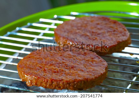 Hamburgers over a bbq, focus over low part of first hamburger - stock photo