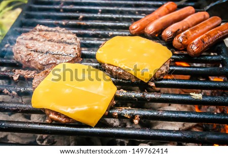 hamburgers with cheese and hot dogs on grille on camping trip - stock photo