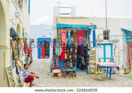 HAMMAMET, TUNISIA - SEPTEMBER 6, 2015: The arabic market offers the colorful clothes, different souvenirs and accessories, on September 6 in Hammamet.