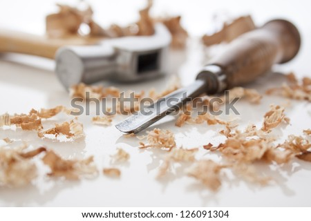 hammer and chisel on a white board with sawdust shavings - stock photo