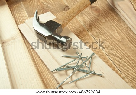 Hammer and nail on a wooden background.