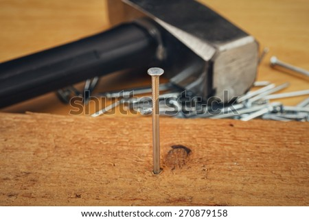 Hammer and nails on wooden board - stock photo