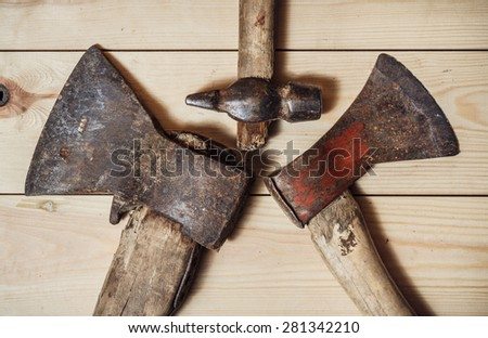 Hammer and two axes on the wooden background. top view - stock photo