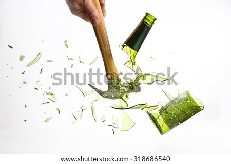 Hammer break a green glass bottle isolated on a white background - stock photo