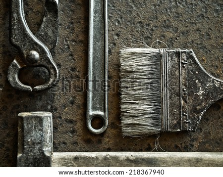 Hammer, brush, pincers and wrench over rusty metal background - stock photo