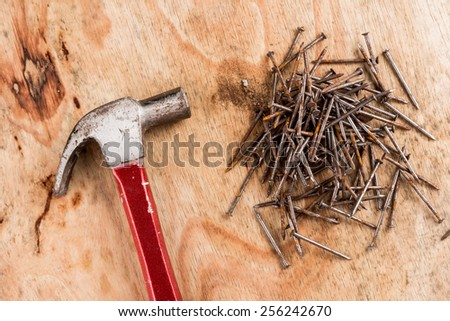 Hammer head and nails on a wooden table. - stock photo